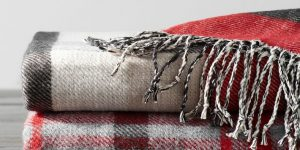 plaid reversible throw blankets stacked on a wooden table.