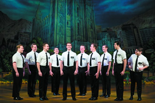 Scene from The Book of Mormon with a circle of Mormon men in black pants, dress shoes, a black tie, and a white short sleeved button up shirt.