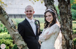 Manny (left) and Molly (right) Cohen on their wedding day posing between tree branches. They smile with arms crossed in their tuxedo and wedding dress.