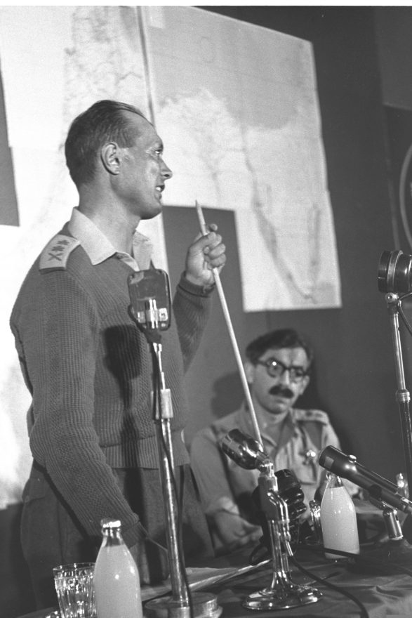 RAV ALUF MOSHE DAYAN HOLDING PRESS CONFERENCE ON THE SINAI CAMPAIGN. SEATED, SGAN ALUF MOSHE PERLMAN.