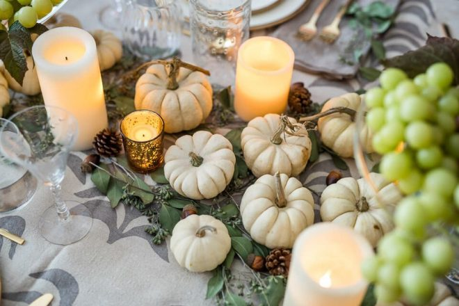 close up on Michele Saulson's table with the candles, acorns, grapes, and small pumpkins as a center piece.