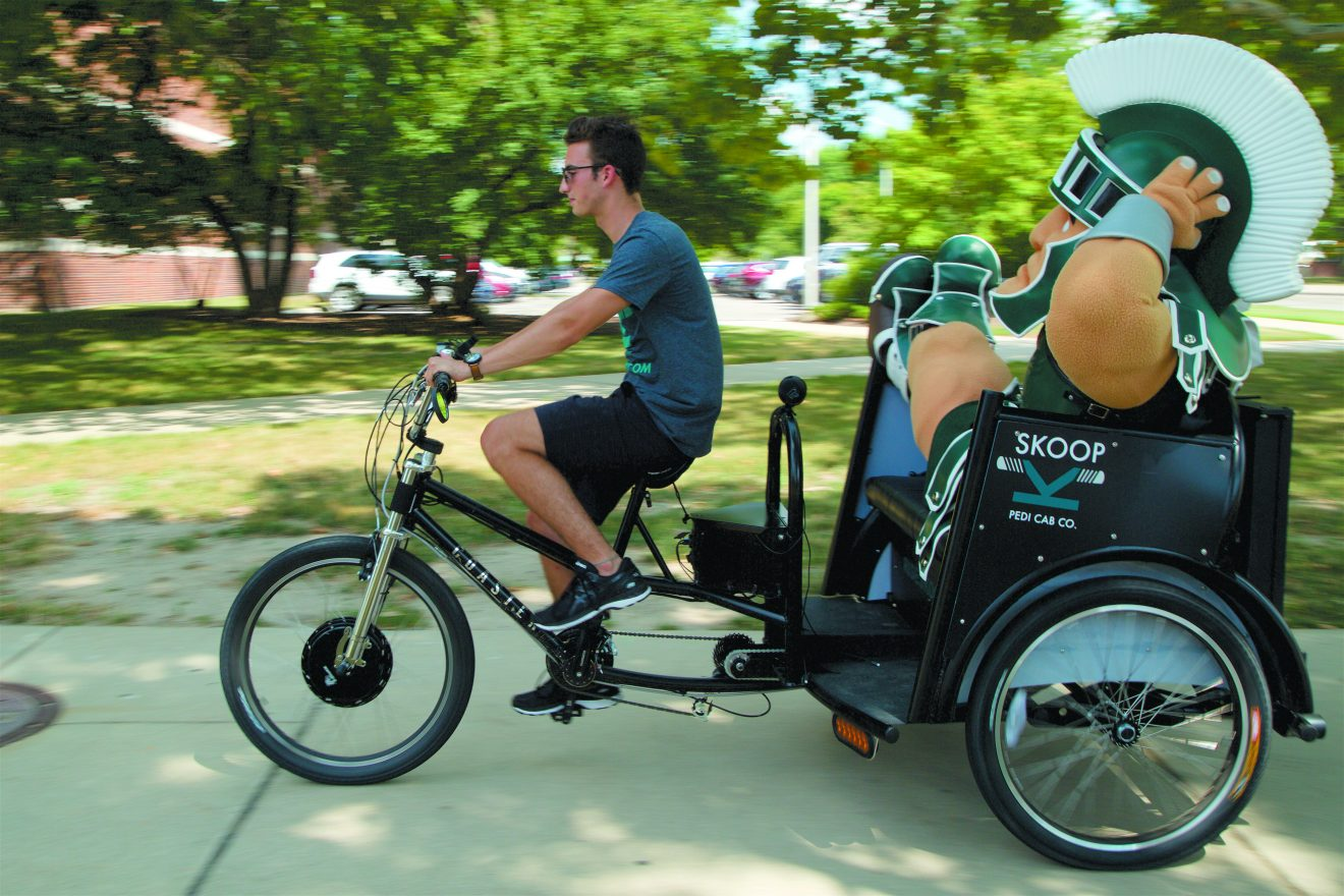 Josh Cooper gives Sparty a ride in one of the SKOOP pedicabs on the MSU campus.