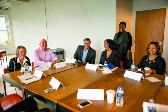 Philanthropists Connie and Steve Ballmer, left, talk with a group of organization representatives including Jeff Edmonson and Katrina McCree at the Commons, a coffee shop and coin laundry in Detroit. Ballmer Group Detroit Executive Director Kylee Mitchell Wells is standing.