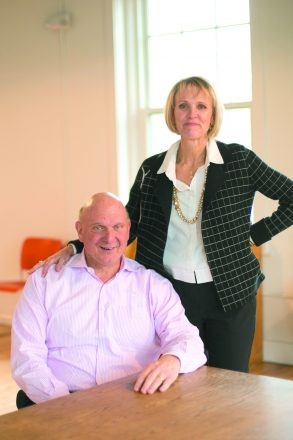 Steve Ballmer sitting in a chair with wife Connie standing beside him with one arm on his shoulder