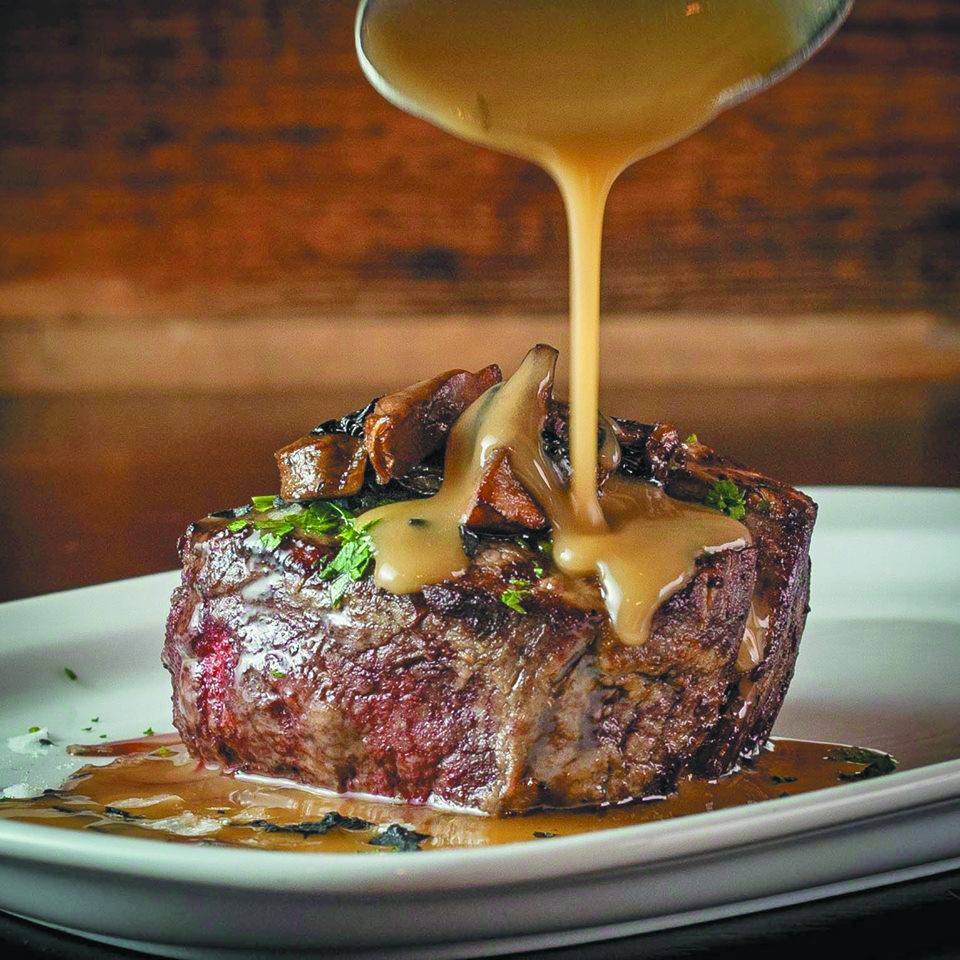 filet of steak with mushrooms on top and a sauce or gravy being poured from a spoon above all resting on a plane oval plate.