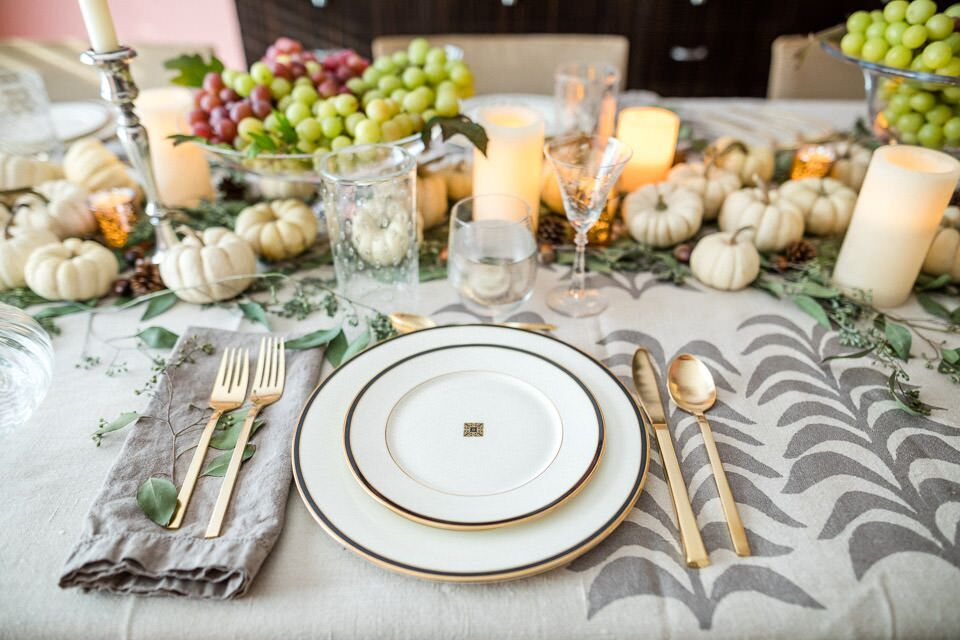 A place setting and the dinner table at Michele Saulson's house with small pumpkins, grapes, and candles.