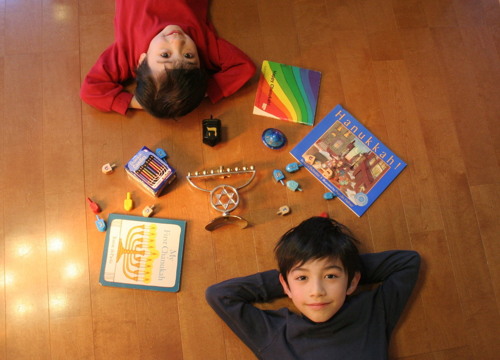 a girl and boy lay on the floor in opposite directions and smile up at a camera above with a menorah, gelt, dreidels, candles, and chanukah books between them.