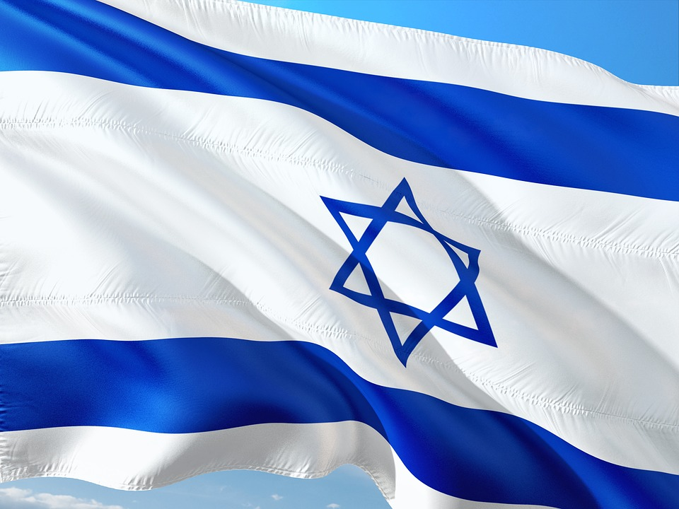 close-up on the Israeli flag waving (a white and blue flag with a horizontal stripe at the top and bottom and a star of David in the middle)