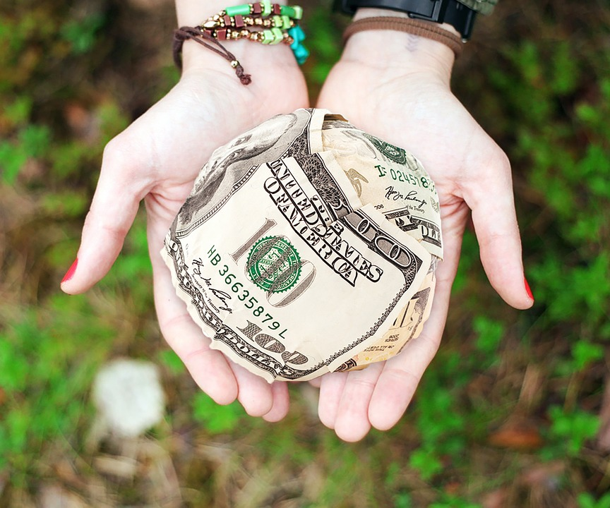 two outstretched hands holding a paper ball of money over a grassy area.