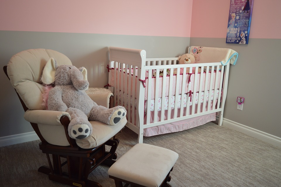 nursery with a crib and a rocking chair with a giant stuffed elephant in it