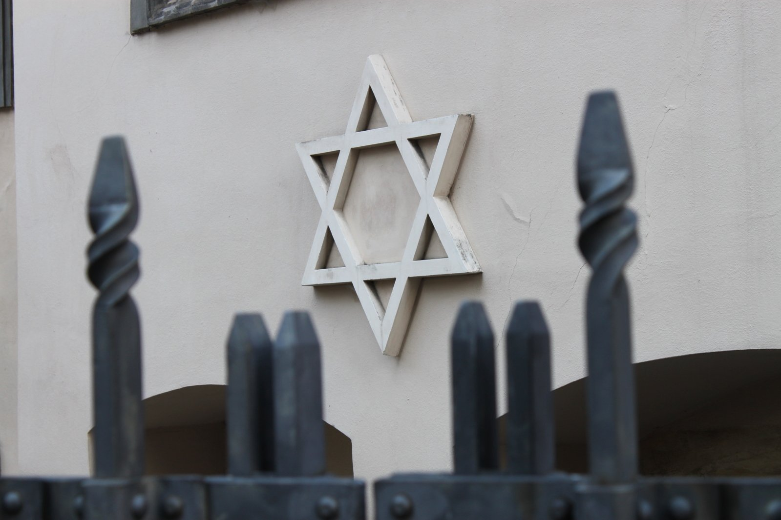 Star of David on a wall seen through an iron fence