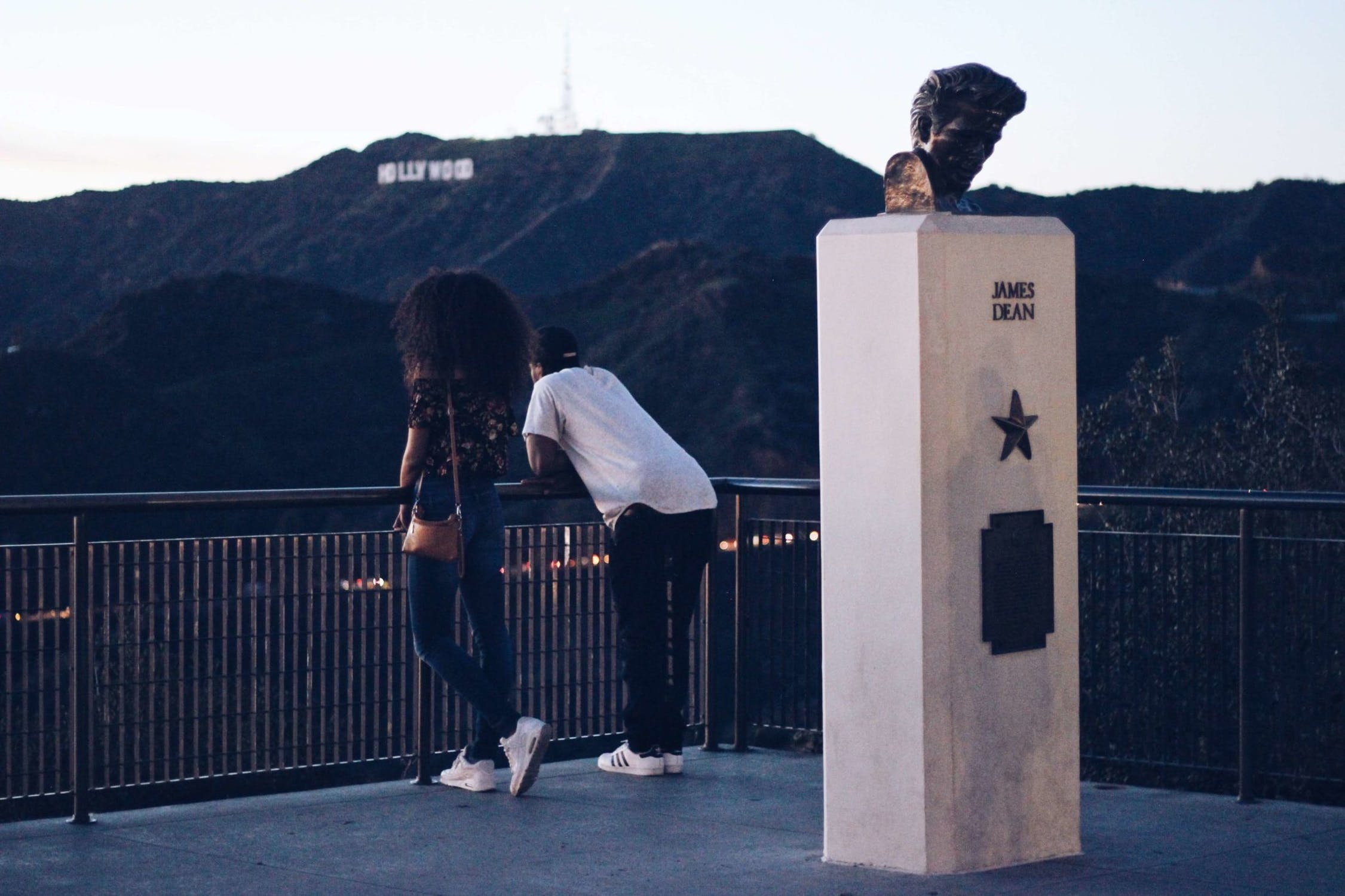 a woman (left) and man (right) stand in front of a James Dean statue and look towards the Hollywood sign on the mountains in Los Angeles.