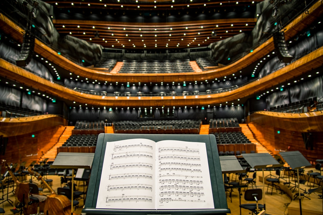 view of an orchestra hall from the point of view of a player with a music stand and a piece of music open on the stand. The concert hall is empty.