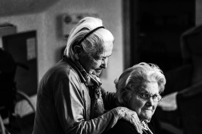 older woman sitting and looking at the camera as another older woman holds onto her shoulders and looks down at her.