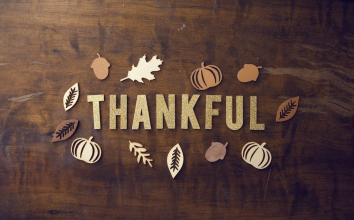 "fall-themed photo of the words ""Thankful"" on a wood table with leaves and pumpkins around it to represent November Here's To."