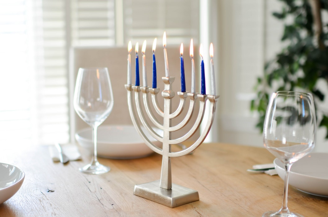 lit menorah on a table with two empty wine glasses.