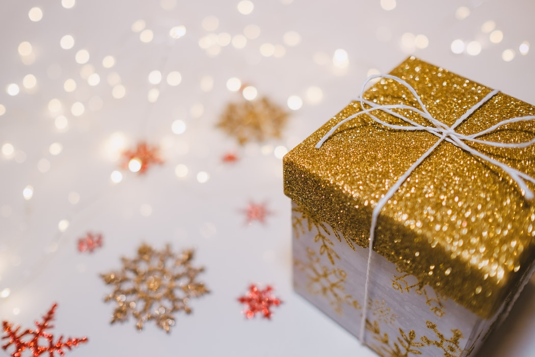 gold and red glittery snowflakes with golden twinkle lights and a present box wrapped with gold wrapping paper on top and a white wrapping paper with gold snowflakes on the bottom and tied with a string ribbon.