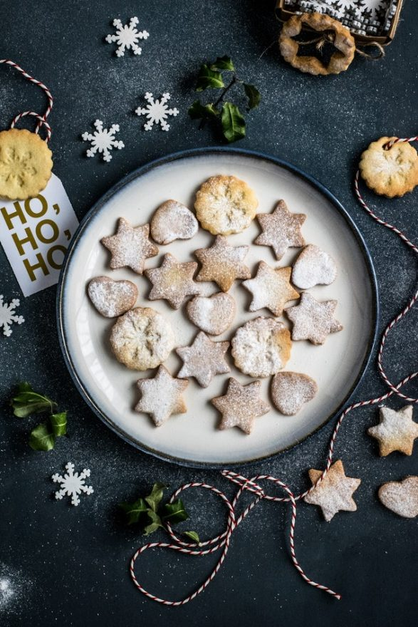 "butter cookies on a plate in the shape of stars of David and circles with snowflakes on them with a dark background with paper snowflakes and red and white string and a noe that says ""ho, ho, ho"""