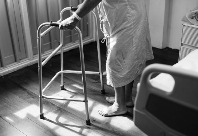 older person seen from the waist down standing in a hospital in a hospital gown holding a walker