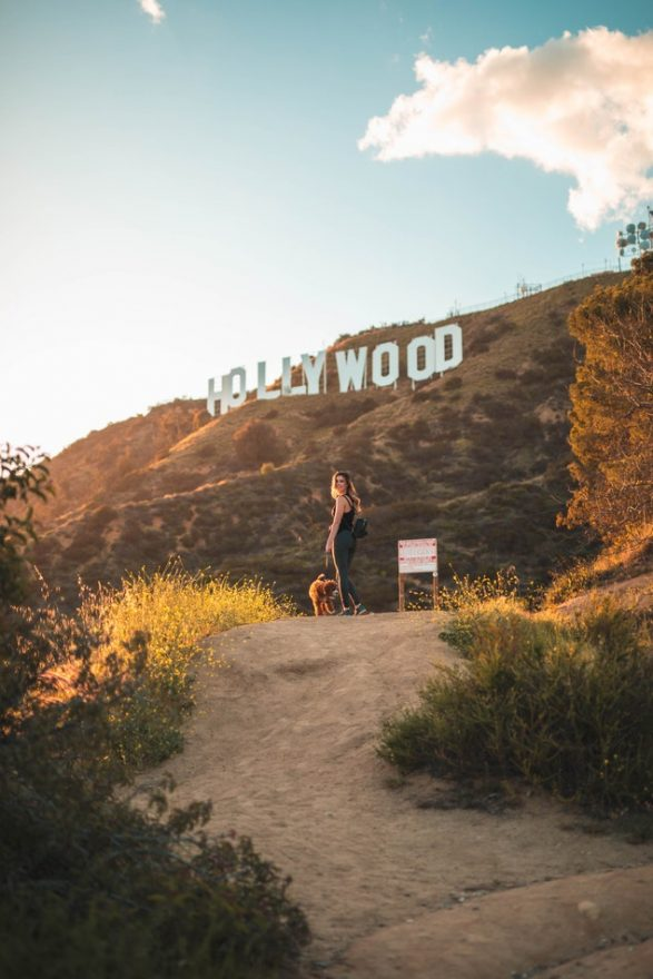 girl and her dog walk up a dirt path with the Hollywood sign in the background.