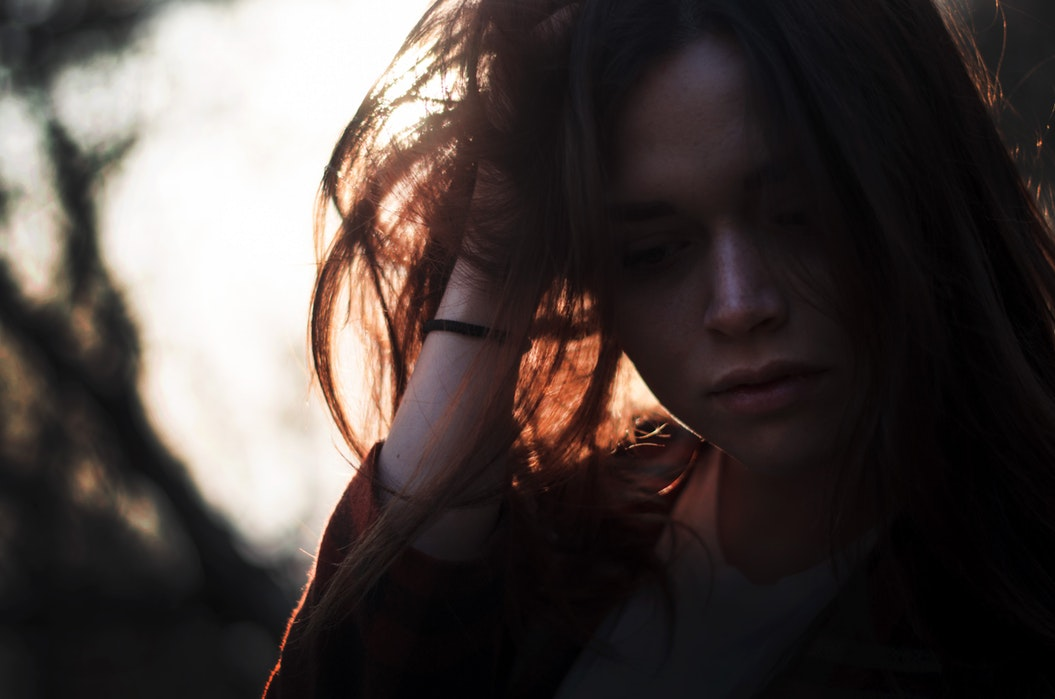 close up on a girl with her hand in her hair and the sun behind her.