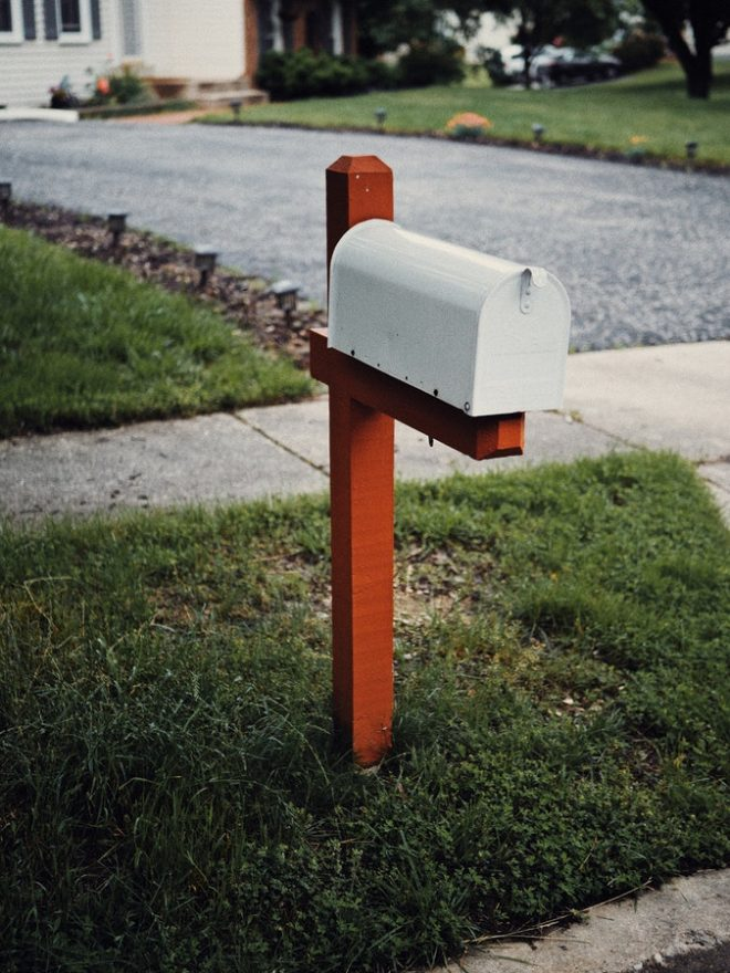 mail box on a grassy lawn near a driveway