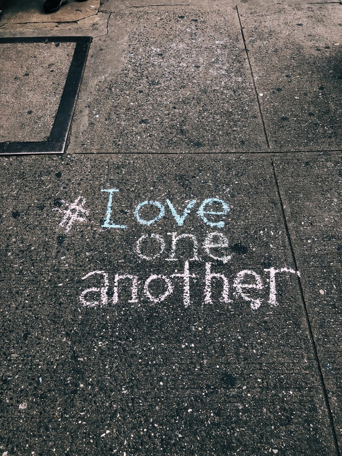 "chalk writing on a sidewalk reading ""#Love one another"" #loveoneanother"