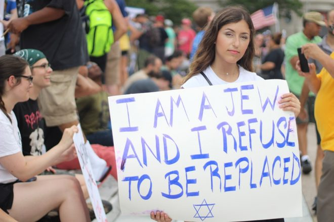 "Woman holding a sign in a crowd of people that reads. "" I am a Jew and I refuse to be replaced"" with a star of David underneath the words."