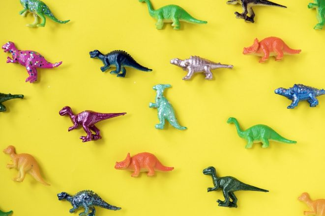 toy dinosaurs lined up on a plain background