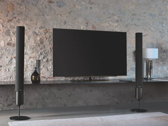 large flat screen TV on a TV stand with two large speakers beside it in a dimly lit room