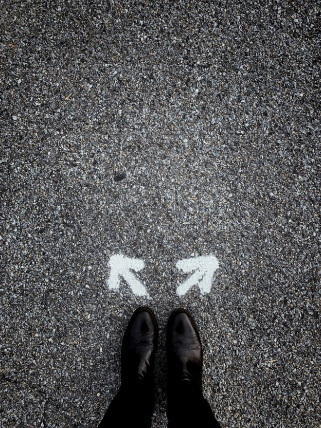 two shoes in front of two arrows pointing in opposite directions on a gravel ground.