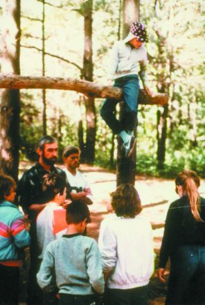 Randy Childs sitting on a tree log in the air while people stand around and watch