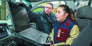 Oak Park Police Officer James Vernier shows Yael Chimovitz, 16, of Oak Park the equipment inside his police car.