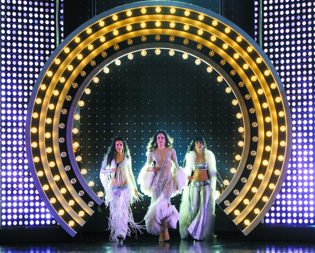 Scene from The Cher Show with cher in the middle and two women beside her as they enter the stage under a cured light tunnel. The women are all wearing sequined and glittery outfits with feather boas and fringe.