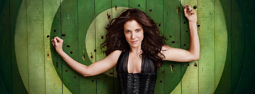 Nancy Botwin (Mary-Louise Parker) in Weeds stands against a green bullseye in a low cut top with flowing hair