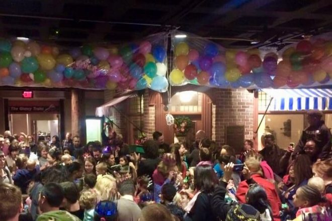 Noon Year's Eve party at the Detroit Historical Society showing balloons and a lot of kids sitting on the floor.