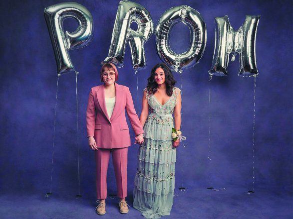 "Photo of two women wearing a pink dress suite and a dress under balloons that spell ""prom"""