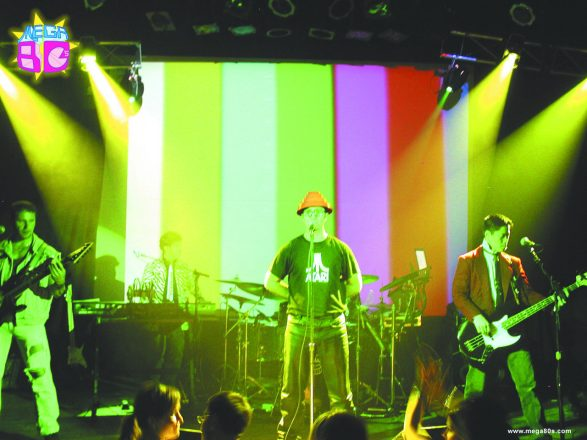 '80s cover band playing with a rainbow backdrop and lights