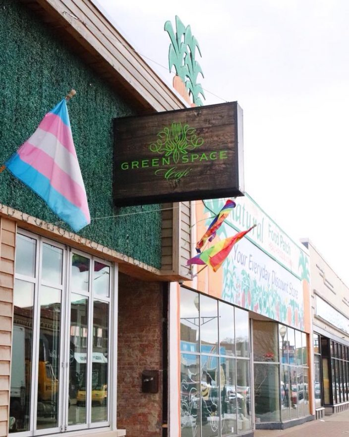 GreenSpace Cafe store front showing the sign for the restaurant and a flag in Ferndale, MI