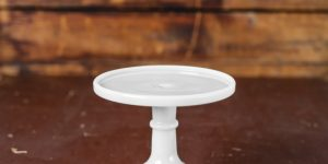 white cake stand on a wooden table