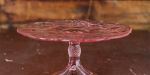 pink glass cake stand on a wooden table
