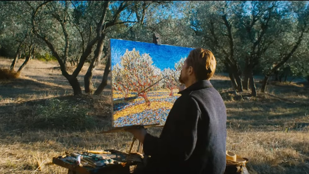Still from the movie At Eternity's Gate showing Vinvcenrt van Gogh painting trees in a tree-filled area