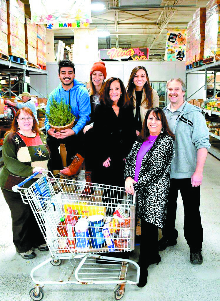 The Yad Ezta staff at Yad Ezra with a shopping cart full of groceries.