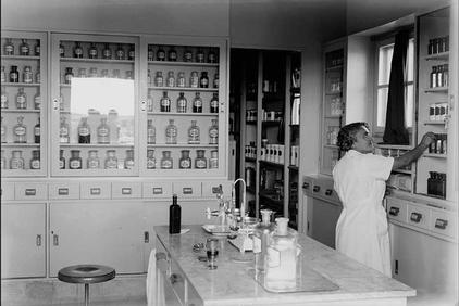 A Kupat Holim Clalit pharmacy operates at Kfar Saba in 1938. Here we see the Kupat Holim Clalit pharmacy with bottles of meidicne in the background and a pharmacists organizing on the side.