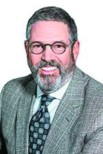 David Techner - male with beard and glasses smiles in suit