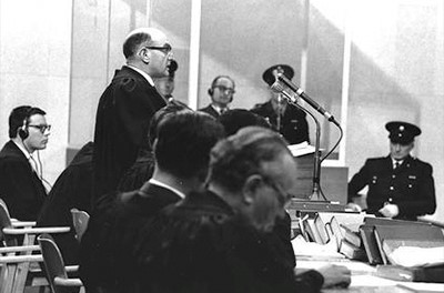 Prosecutor Gideon Hausner delivers his closing remarks while defendant Adolf Eichmann watches from a glass box in the background in 1961.