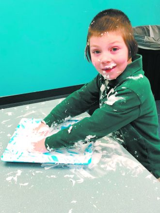 Yosef plays in shaving cream at The Spot, a program of the Detroit Chesed Project