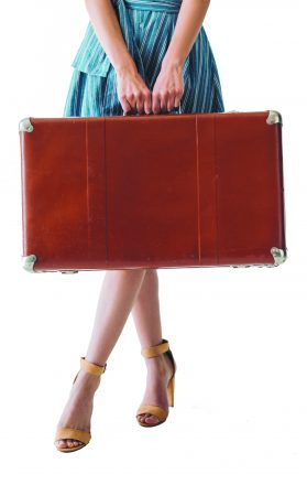 partial view of woman holding retro suitcase isolated on grey