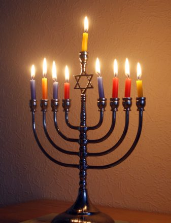 lit menorah with all 9 candles lit and a star of david in the middle