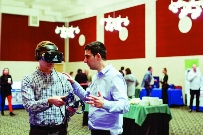 An Israeli innovator shows an MSU student how his product works while the student wears a VR device over his eyes.